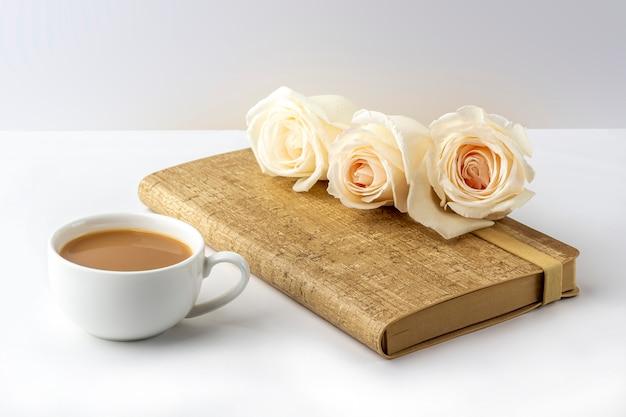 Plat lag bloemen romantische samenstelling. 's ochtends koffiemok voor ontbijt, notebook en witte rozen. vrouwelijke werkplek.
