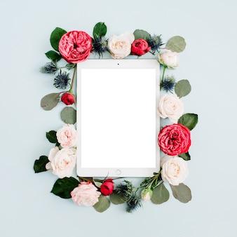 Plat lag bloemenkader met tablet, rode en beige roze bloemknoppen op bleke pastelblauw