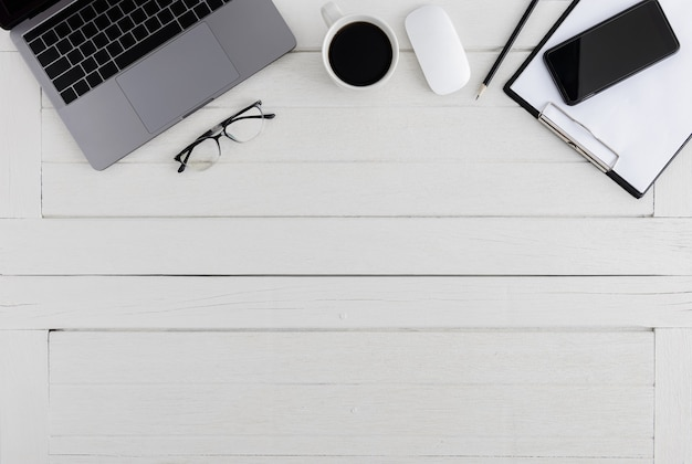 Plat lag, bovenaanzicht houten bureau. werkruimte met leeg klembord, laptop, muiscomputer, smartphone, bril, koffiekopje kantoorbenodigdheden