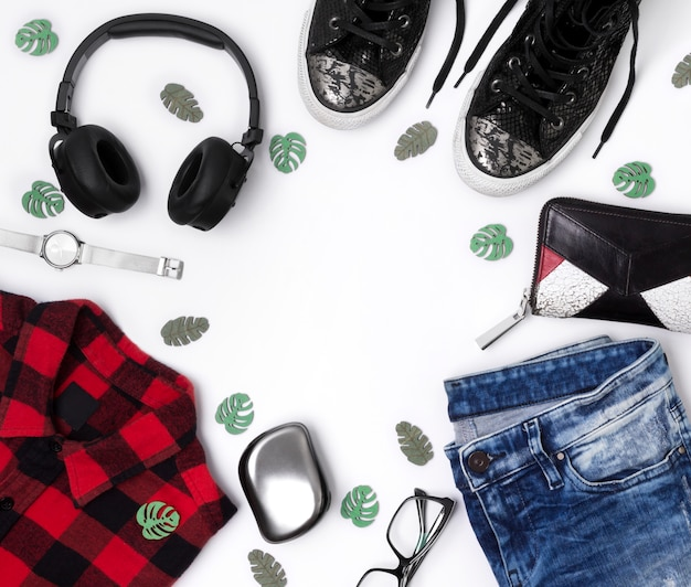 Plat lag bovenaanzicht in vrouwelijke stijl met geruite t-shirt, jeans, sneakers, horloges, kam, bril, portemonnee en koptelefoon