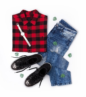 Plat lag bovenaanzicht in vrouwelijke stijl met geruite t-shirt, jeans, sneakers, horloges
