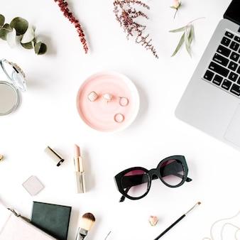 Plat lag, bovenaanzicht kantoor tafel bureau frame. vrouwelijke bureau werkruimte met laptop, clutch, cosmetica, telefoon, zonnebril, lippenstift roze toppen op witte achtergrond.