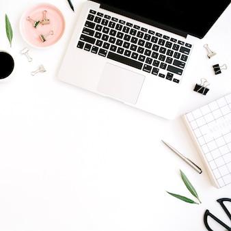 Plat lag, bovenaanzicht kantoortafel bureau. werkruimte met notitieboekje, laptop, palmtak, koffiekopje, schaar en clips op witte achtergrond.