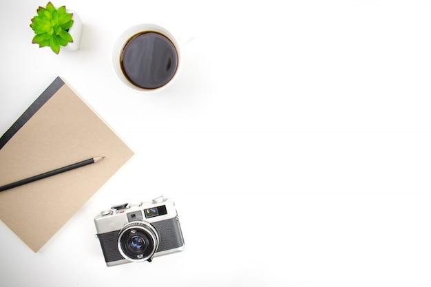Plat lag, bovenaanzicht met filmcamera, laptop en koffie op een wit bureau.