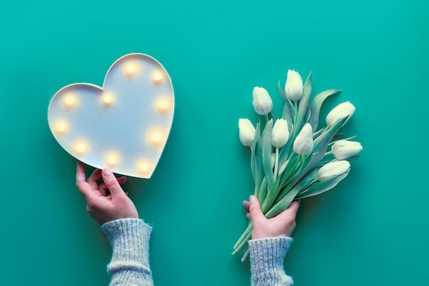 Plat lag, bovenaanzicht met hand met plastic hartvormige lightboard met verlichting en bos van witte tulpen