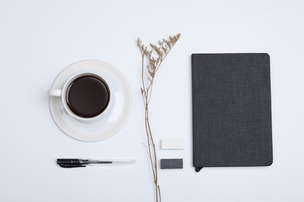 Plat lag, bovenaanzicht modern wit bureau tafel. zwart boek, witte kop koffie, pen, rubber en droge bloem op witte achtergrond