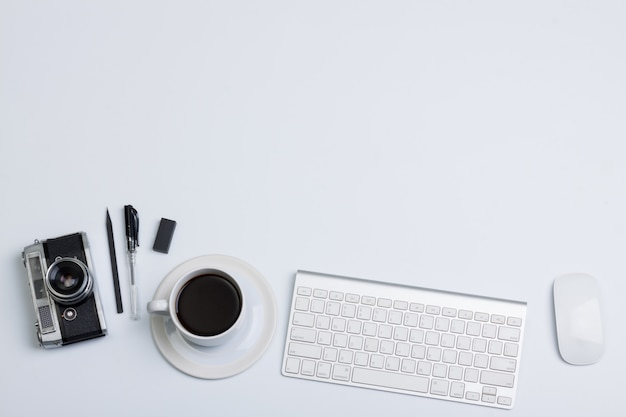 Plat lag, bovenaanzicht moderne kantoor tafel bureau. camera koffie en toetsenbord muis op witte achtergrond