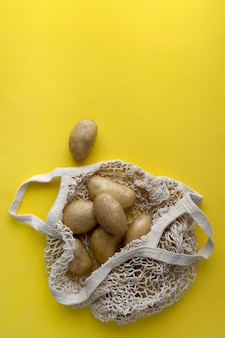 Plat lag bovenaanzicht rauwe biologische aardappelen in string zak op gele achtergrond