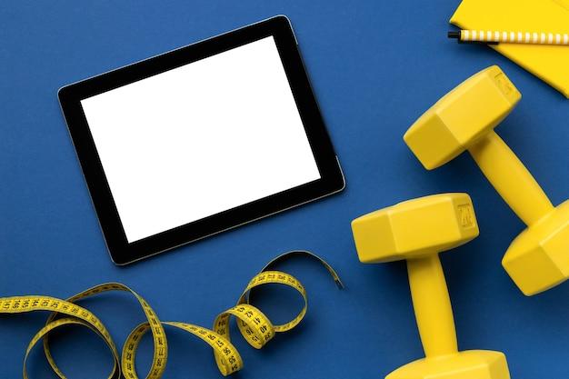 Plat lag bovenaanzicht tablet met gele sportuitrusting op klassiek blauw oppervlak