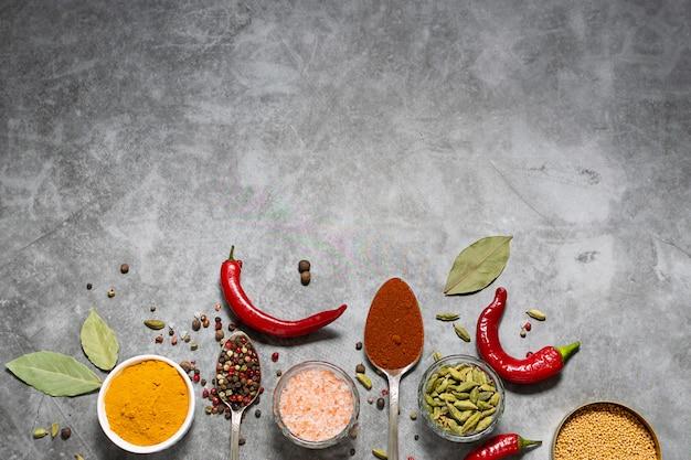 Plat lag bovenaanzicht van biologische aromatische specerijen en kruiden op zwart marmeren tafel.
