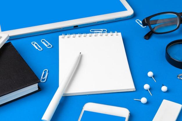 Plat lag, bovenaanzicht van blauwe office tafel bureau, werkruimte met blanco notitieboek, kantoorbenodigdheden