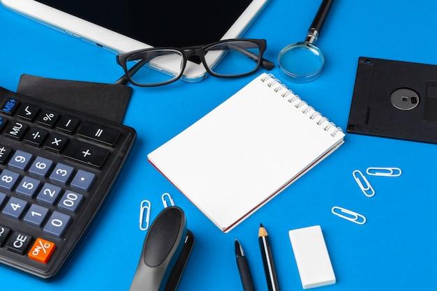 Plat lag, bovenaanzicht van blauwe office tafel bureau. werkruimte met lege notitieboek, kantoorbenodigdheden