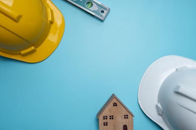 Plat lag, bovenaanzicht van bouw- of onroerend goed bedrijfsconcept met gele en witte helm en klein houten huis en inwoner, kopen van onroerend goed, huis, bouwgereedschap op blauwe muur