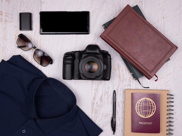 Plat lag bovenaanzicht van reiziger accessoires op witte houten achtergrond. digitale camera, shirt, boeken, smartphone, papieren notitieboekje met pen, zonnebril en paspoort