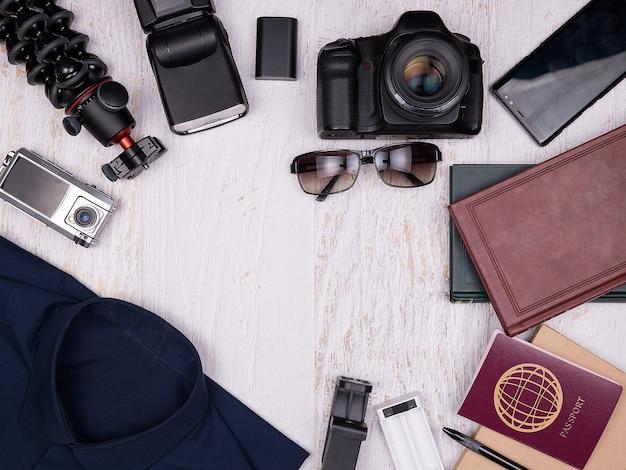 Plat lag bovenaanzicht van reiziger accessoires op witte houten achtergrond. digitale en actiecamera, shirt, boeken, smartphone, papieren notitieboekje met pen, zonnebril en paspoort