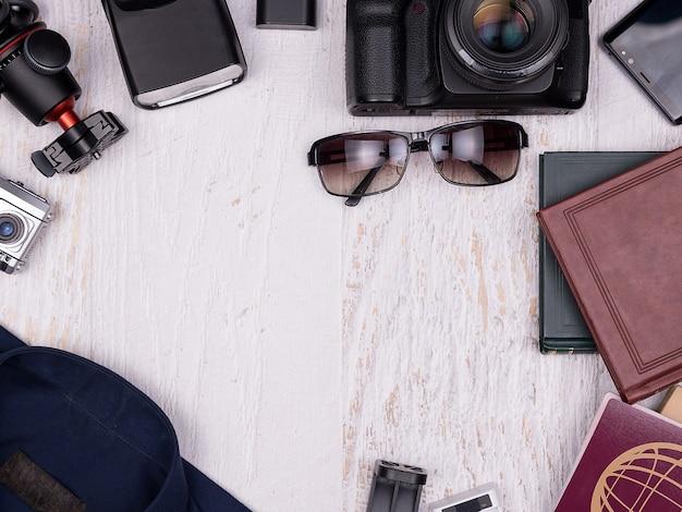 Plat lag bovenaanzicht van reiziger accessoires op witte houten achtergrond. digitale en actiecamera, statief, shirt, boeken, smartphone, papieren notitieboekje met pen, zonnebril en paspoort