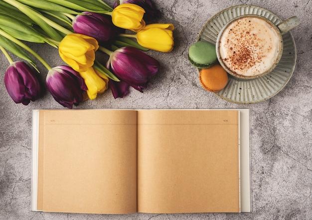 Plat lag, bovenaanzicht van vrouwelijk bureau. koffiekopje voor het ontbijt, tulpen, bitterkoekjes, lege notebook. planning ontbijt bedrijfsconcept.