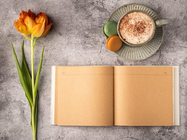 Plat lag, bovenaanzicht van vrouwelijk bureau. koffiekopje voor ontbijt, bitterkoekjes, lege notebook, oranje tulp. planning ontbijt bedrijfsconcept.