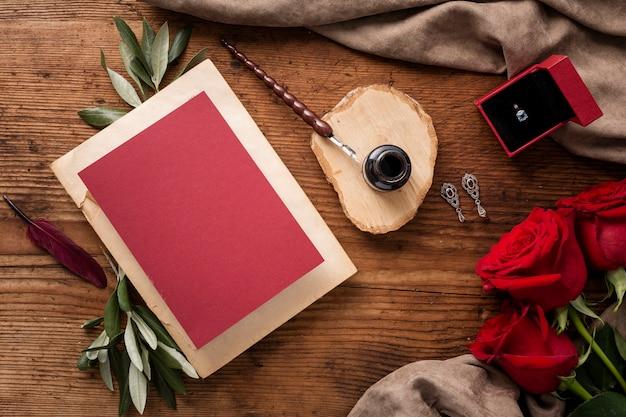 Plat lag bruiloft kaart en rozen op tafel