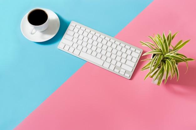 Plat lag bureau tafel van moderne werkplek met laptop op blauwe en roze tafel,