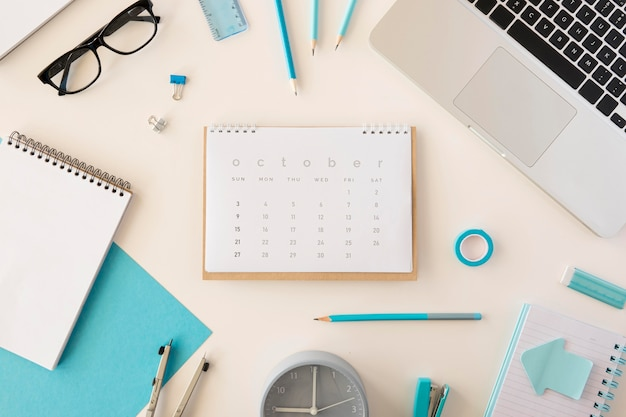 Plat lag bureaukalender met blauwe kantooraccessoires