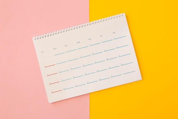 Plat lag bureaukalender op gele en roze achtergrond