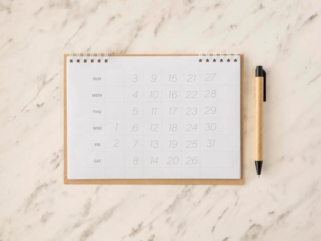 Plat lag bureaukalender op marmeren tafel