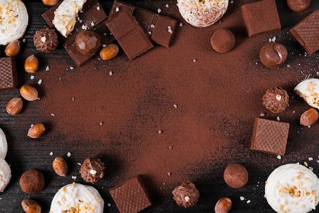 Plat lag chocolade snoep mix en cacaopoeder op roze achtergrond met kopie ruimte