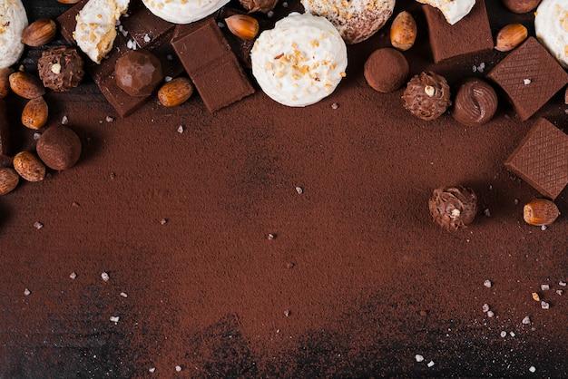 Plat lag chocolade snoepjes assortiment en cacaopoeder op roze achtergrond met kopie ruimte