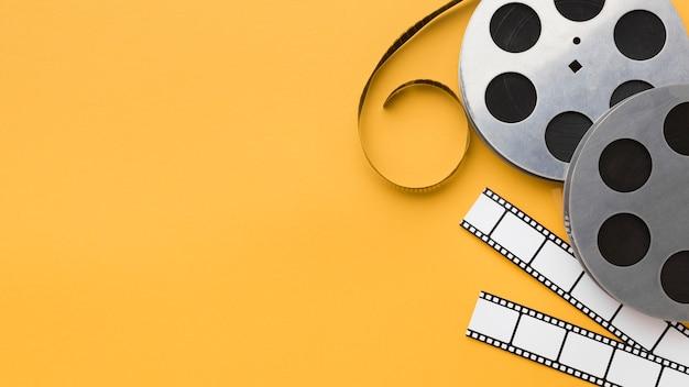 Plat lag cinema-elementen op gele achtergrond met kopie ruimte