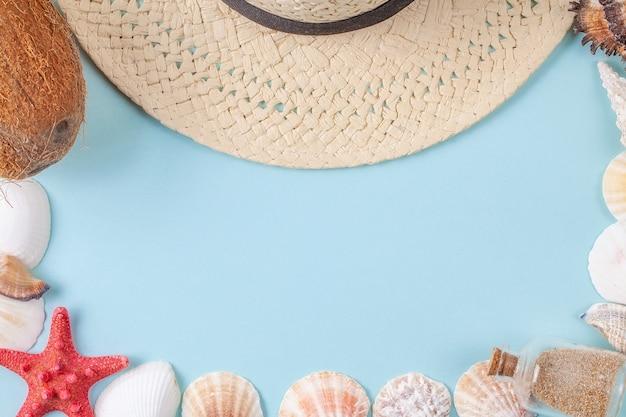 Plat lag compositie met prachtige zee-elementen en strooien hoed op een blauwe achtergrond