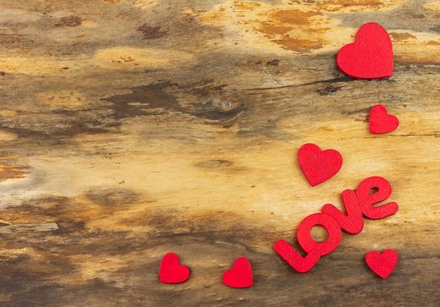 Plat lag compositie met rood woord liefde en zes harten in de rechter benedenhoek op een natuurlijke houten achtergrond voor valentijnsdag.