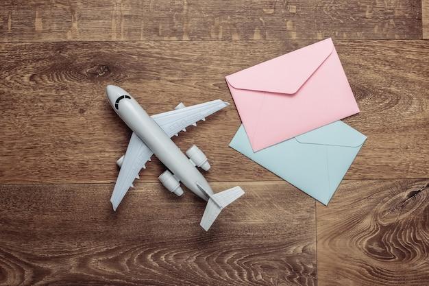 Plat lag compositie met vliegtuig figuur en enveloppen met letters op houten vloer.