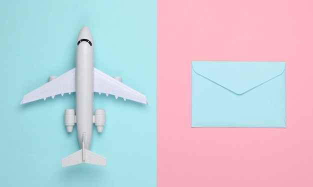Plat lag compositie met vliegtuig figuur en enveloppen van letters op roze blauw pastel.
