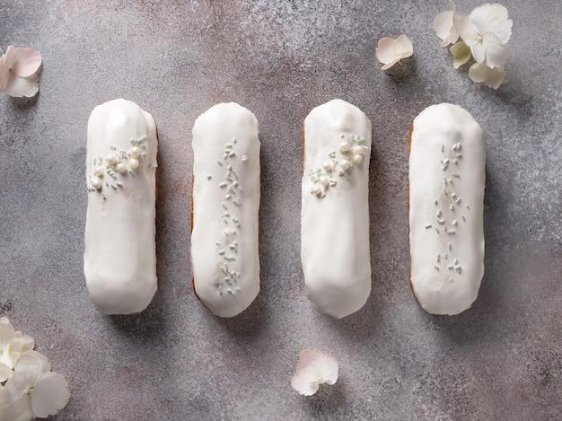 Plat lag compositie met witte chocolade glazuur eclairs en hortensiabloemen. gebak gevuld met room.
