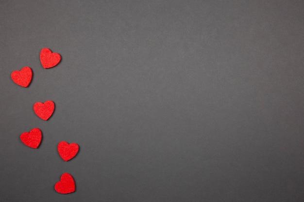 Plat lag compositie voor valentijnsdag, moederdag of bruiloft met rode harten op donker.