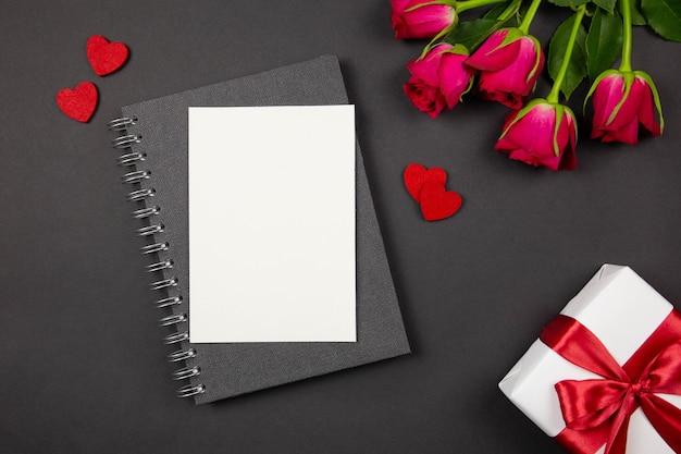 Plat lag concept van valentijnsdag, jubileum, moederdag en verjaardagsgroet met wenskaart en geschenkdoos met rood lint, harten, rozen op donker.