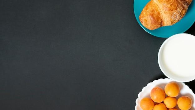 Plat lag croissant, melk en abrikozen op effen achtergrond met kopie ruimte