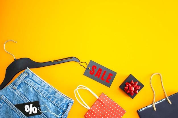 Plat lag, detail van spijkerbroek met label en inscriptie verkoop cadeauzakjes op gele achtergrond.