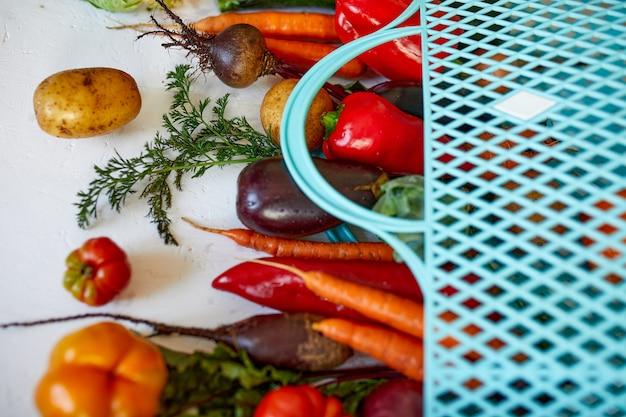 Plat lag eco-vriendelijke boodschappentas met assortiment van verse groenten, bio gezond, biologisch voedsel op witte achtergrond, landelijke markt stijl, kruidenier, dieet vegetarisch voedsel, schoon eten.