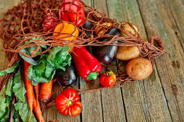 Plat lag eco-vriendelijke string shopping herbruikbare mesh tas met assortiment van verse groenten, bio gezond, biologisch voedsel op houten achtergrond, landelijke markt stijl, kruidenier, dieet vegetarisch voedsel.