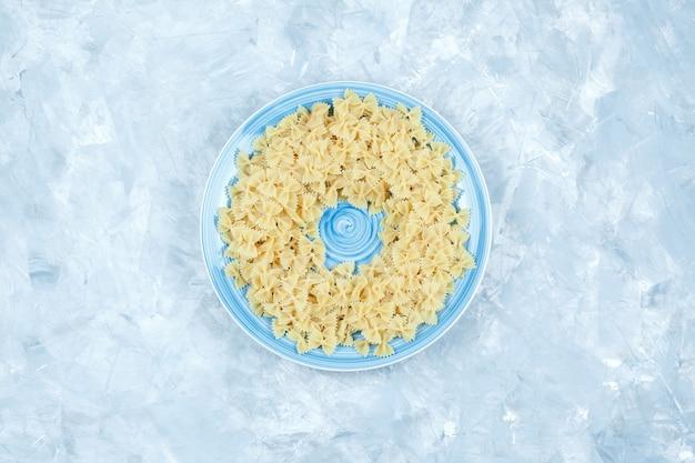 Plat lag farfalle pasta in plaat op gips achtergrond. horizontaal