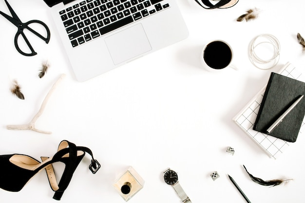 Plat lag fashion blogger zwart gestileerd bureau frame met laptop en vrouw accessoire collectie op wit