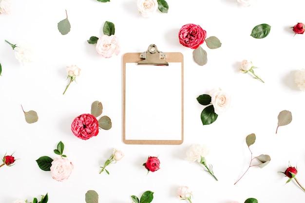 Plat lag floral frame met klembord, rood en beige roze bloemknoppen patroon op wit