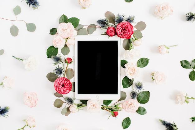 Plat lag floral frame met tablet, rode en beige roze bloemknoppen op wit