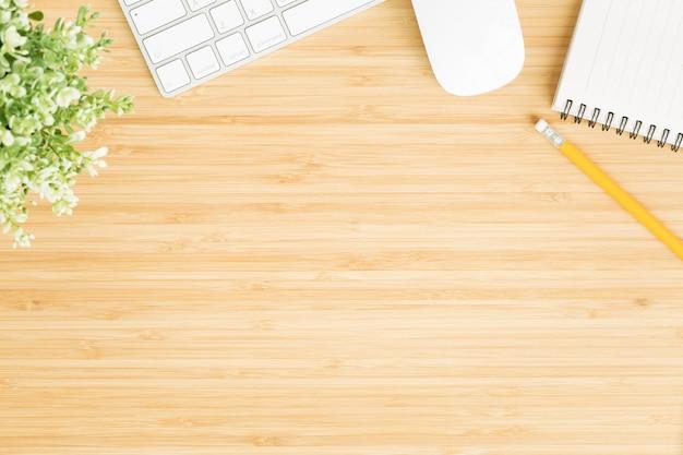 Plat lag foto bureau met muis en toetsenbord, bovenaanzicht bamboe houten tafel en kopie sp
