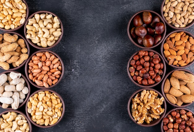 Plat lag geassorteerde noten en gedroogde vruchten in verschillende mini kommen met pecannoten, pistachenoten, amandel, pinda