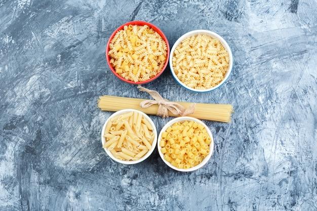 Plat lag geassorteerde pasta in kommen op grungy gips achtergrond. horizontaal