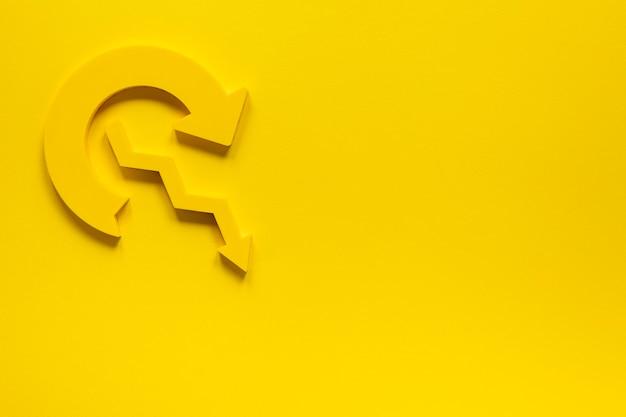 Plat lag gele pijl op gele achtergrond met kopie-ruimte