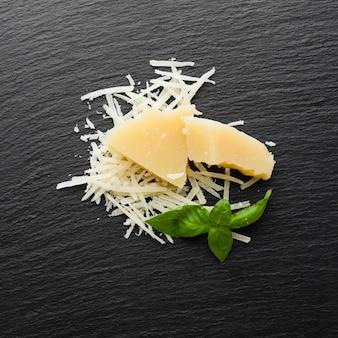 Plat lag geraspte parmezaanse kaas op zwarte achtergrond
